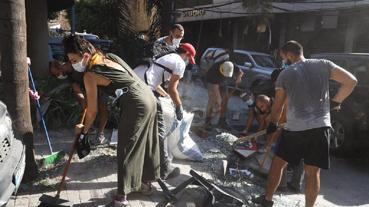 أفراد يشاركون في إزالة الركام في شارع الجميزة المدمر في بيروت