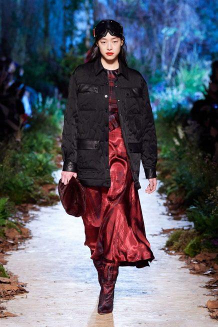 تنورة طويلة مصممة من القماش الخمري اللماع نسقت مع البلوزة ذات نقشة الكارو العريضة ومعهما الجاكيت الطويلة السوداء.
