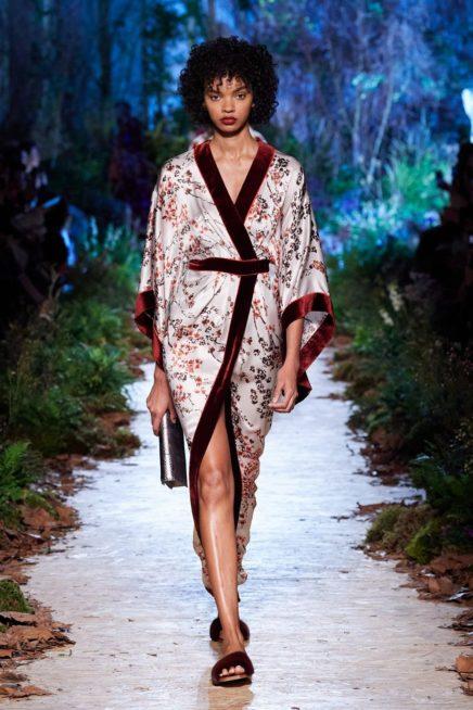 فستان طويل بقصة الكيمونو صمم من الساتان الابيض المزين بنقشا الازهار الناعمة الملونة مع الاطراف المصممة من الجوخ الناعم باللون الخمري.