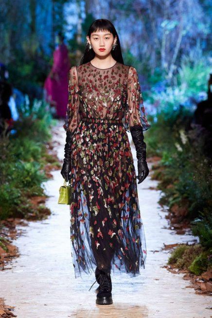 فستان طويل ذات القصة الواسعة صمم من القماش الشفاف المزين باشكار الازهار الملونة التي تغطيه بالكامل ومعه القفازات الجلدية السوداء.