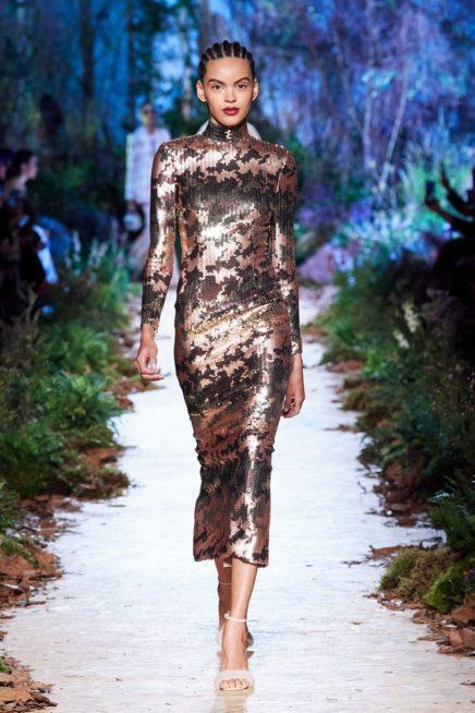 فستان ميدي ذات القصة الضيقة المتناغمة مع الجسم يتميز بلونه البرونزي اللماع مع النقشات السوداء الناعمة مع الياقة العالية.