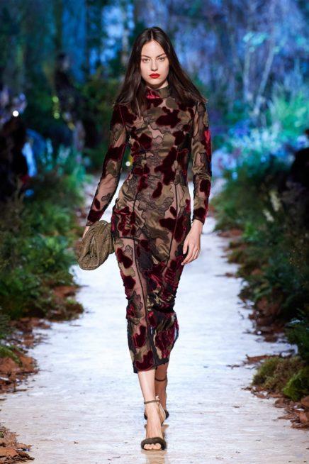 فستان ميدي ضيق مصمم من القماش الشفاف المزين بالنقشات الكبيرة على شكل ازهار صممت من المخمل والجوخ الناعم.