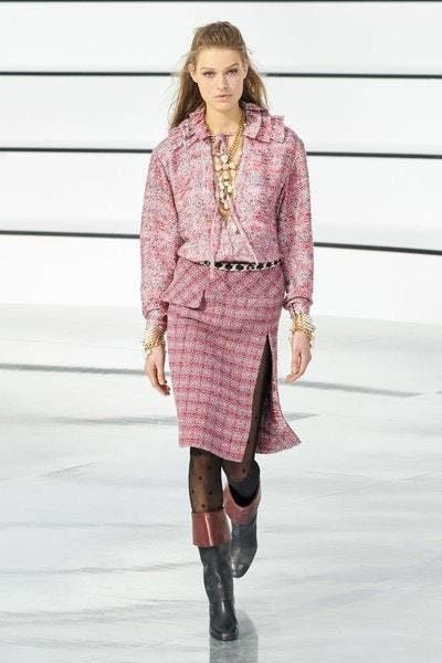 تنورة زهرية اللون ذات قصّة مستقيمة مع الشق الجانبي العالي منسقة مع البلوزة الزهرية ايضاً المزينة بالكشاكش عند الياقة.