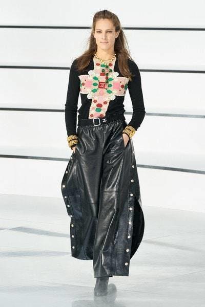 سروال اسود واسع مصمم من القماش الجلدي يتميز بارجله الواسعة المفتوحة عند الجانبين نسق مع البلوزة السوداء المزينة بنقشات ملونة عند الجهة الامامية.