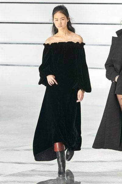فستان طويل اسود اللون مصمم من الجوخ الناعم ذات القصة الواسعة المنسدلة بتناغم مع الجسم مع الاكتاف المكشوفة.