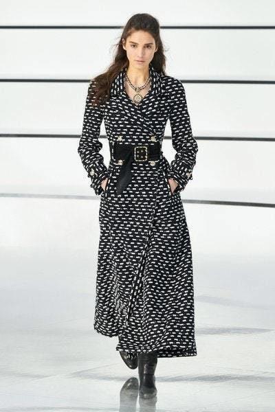 فستان طويل باللون الاسود مع نقشة النقاط البيضاء التي تغطيه بالكامل، يزينه الحزام القماشي الاسود العريض عند الخصر.