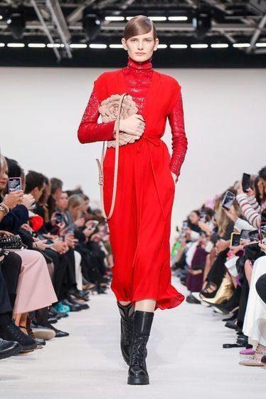 "<p style=""text-align: justify;"" dir=""RTL"">يظهر في هذه الصورة فستان أحمر بفتحة عند الصدر ونرى تحته بلوزة بأكمام طويلة وقد صنعت من قماش مخرّم. أما البوتس فأخذ طابعاً ذكورياً بعض الشيء ليتماهى مع عنوان مجموعة أزياء فالنتينو الجاهزة للعام 2020.</p>"
