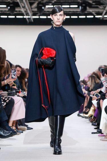 """<p style=""""text-align: justify;"""" dir=""""RTL"""">فستان كحلي رائع وراقي أتى على شكل كاب واسع وطويل. نراه بكم واحد في حين نسّق معه قفازات جلدية سوداء وبوتس عالي، ما عزز من جمال الإطلالة. أما الحقيبة الحمراء، فوجودها كان كفيلاً بإضفاء لمسة من الحيوية على مجمل الستايل. </p>"""