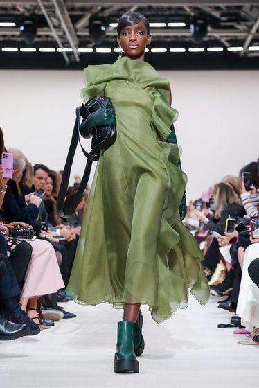 """<p style=""""text-align: justify;"""" dir=""""RTL"""">قطعة مميزة اخترناها لك من مجموعة أزياء فالنتينو الجاهزة لخريف الـ2020، وقد صنع هذا الفستان من قماش الأورغانزا الزيتي وتميز بقصته الواسعة في الأسفل والكشاكش التي تزين المساحة الموجودة ما بين الصدر والأكتاف.</p>"""