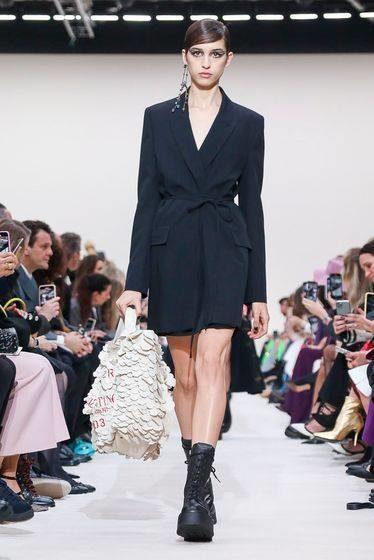"""<p style=""""text-align: justify;"""" dir=""""RTL"""">الفستان المستوحى من بدل الرجال وهو قطعة رائجة في عالم الموضة منذ فترة. نراه بجيب من اليمين واليسار وبشريط عند منطقة الخصر ساهم في تعزيز أناقة الإطلالة وجمالها. وقد نسّق معه البوتس الضخم والذي يعد من القطع الأبرز في مجموعة أزياء فالنتينو الجاهزة لخريف 2020.</p>"""