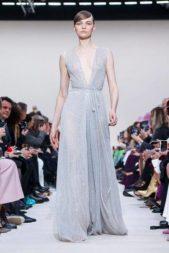"""<p style=""""text-align: justify;"""" dir=""""RTL"""">من بين مجموعة أزياء فالنتينو الجاهزة لخريف 2020، رصدنا لك قطعة رائعة تضج أنوثة وجمالاً. تأملي هذا الفستان الطويل الناعم الذي صنع من الترتر وسيطر عليه اللون الأزرق السماوي. ونراه بفتحة عند الصدر وبشريط حدد الخصر ما زاد من جمال الطلة.</p>"""