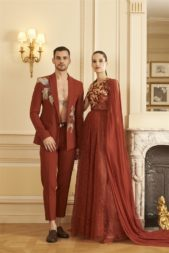 "<p dir=""RTL"">اطلالة أخرى منسّقة بين الرجل والمرأة وتعتمد تحديداً على اللون الموحّد. ويبدو الفستان في غاية الاناقة مع قماش الدانتيل المنسدل في قسمه السفلي، الكورسيه المطرّز وشلحة الموسلين على جانب واحد.</p>"