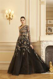 """<p dir=""""RTL"""">فستان طويل للسهرات باللون الأسود، تزيّنه التطريزات الملوّنة والبراقة المستوحاة من عناصر الطبيعة المختلفة. وهو يأتي بقصّة الكتف الواحد.</p>"""
