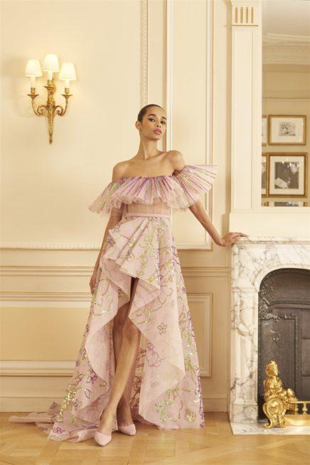 """<p dir=""""RTL"""">فستان يعكس حبّ السهر، فهو يأتي باللون الزهري الفاتح لكن اللافت فيه الياقة المفتوحة المصمّمة بالكشكش المطرّز بالخيوط البرّاقة، وستايل القسم السفلي المتفاوت الطول والذي يعتمد ايضاً على التموّجات في القصّة.</p>"""