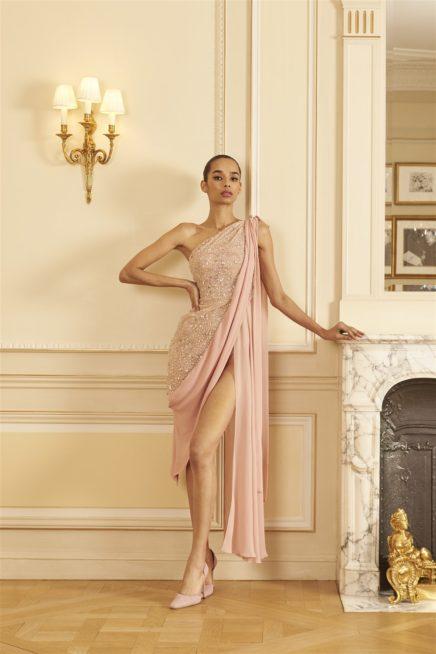 "<p dir=""RTL"">فستان مثير من تصميم جورج حبيقة يعتمد الستايل الروماني من ناحية الكتف الواحد وشلحة الموسلين المنسدلة من الجانب الآخر، واللافت فيه الشقّ العالي جداً على الساق.</p>"