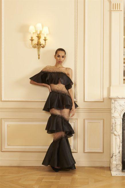 """<p dir=""""RTL"""">فستان طويل رائع بتصميمه الذي يمزج القماش الشفاف مع القماش المموّج الذي يلتفّ حول الجسم بطريقة مذهلة. وقد أضيفت حبيبات الترتر الى الأقسام الشفافة.</p>"""