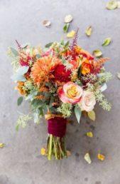 """<p style=""""text-align: right;"""" dir=""""RTL"""">مسكة عروس مميزة تسيطر عليها الألوان النارية كالبرتقالي والخمري. ونرى هنا تشكيلة منوّعة من الورود والأزهار زات الألوان التي تليق بالربيع، في حين زاد شريط الستان الخمري الموجود عند قبضة الباقة من تميز هذه المسكة العرائسية الملفتة.</p>"""