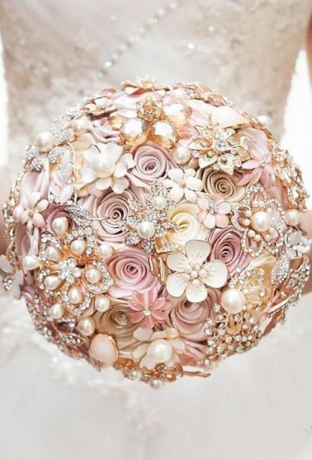 "<p style=""text-align: justify;"" dir=""RTL"">مسكة عروس كريستال رائعة أخرى، معمولة من الورود المصنوعة من القماش الملون بالزهري، النيود والأبيض. وقد تزينت الباقة بقطع أكسسوار على أشكال أزهار كبيرة وصغيرة الحجم مرصعة بحبيبات الستراس اللامعة وحبيبات اللؤلؤ الضخمة.</p>"