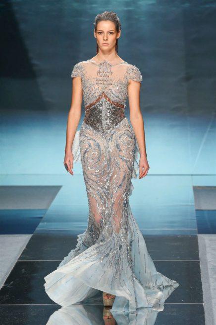 """<p dir=""""RTL""""><span lang=""""AR-LB"""">امواج البحر تتلاطم بشكل فنيّ رائع في هذا الفستان ذات الخامة الشفاف، والذي طرّز كلّه بشكل دقيق ليعكس اجواء مدينة أتلانتيس. ويزداد جمالاً مع شكل الحزام المطرّز ايضاً عند وسطه.</span></p>"""