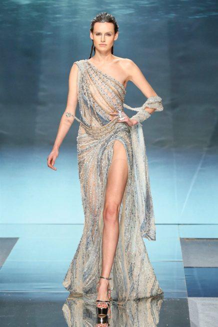 "<p dir=""RTL""><span lang=""AR-LB"">فستان سهرة جريء بتصميمه يعتمد على الشقّ العالي جداً على الساق والكتف المكشوف من جانب واحد. وقد اكتست فيه الخامة الشفافة بالتطريزات البراقة الساحرة للعين والمستوحاة من عالم البحار.</span></p>"