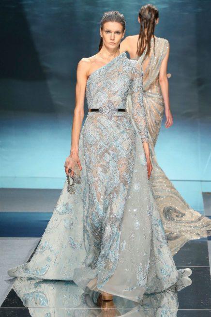 """<p dir=""""RTL""""><span lang=""""AR-LB"""">اللون الأزرق الفاتح المستوحى من البحر يعطي هذا الفستان أناقة لامحدودة، وهو ذات قصّة مستقيمة لكن أضيفت اليه شلحة طويلة، وزيّن خصره بحزام معدني.</span></p>"""