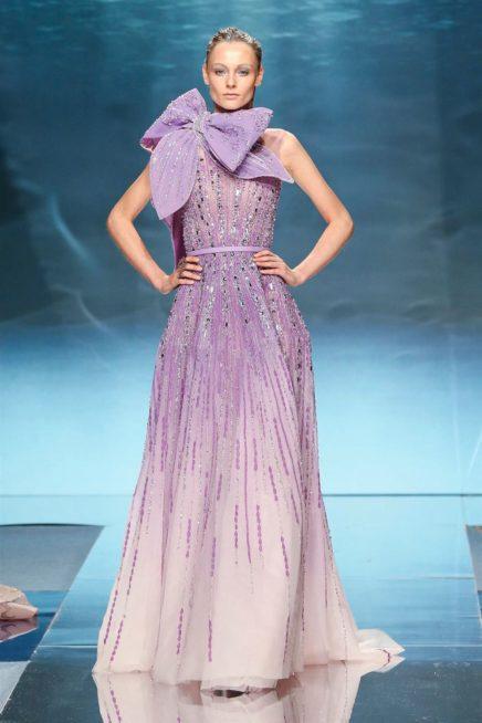 """<p dir=""""RTL""""><span lang=""""AR-LB"""">اللون البنفسجي الناعم حضر ايضاً في عرض زياد نكد، حيث أتى الفستان معتمداً على أكثر من درجة من هذا اللون مع التطريزات البراقة. وأضيفت فيونكة عريضة مربوطة حول العنق.</span></p>"""