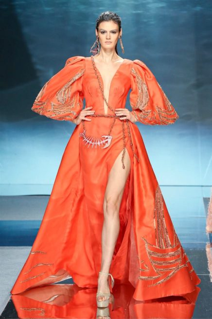 """<p dir=""""RTL""""><span lang=""""AR-LB"""">فستان برتقالي حيوي جداً بتصميمه، يلفت النظر بالرسومات البحرية التي تزيّنه مع الاكمام الواسعة والمنفوخة، وله شقّ مفتوح على الصدر وآخر على الساق. واللافت طبعاً شكل الرباط الذي يلتفّ حوله مع أكسسوار هيكل السمكة.</span></p>"""
