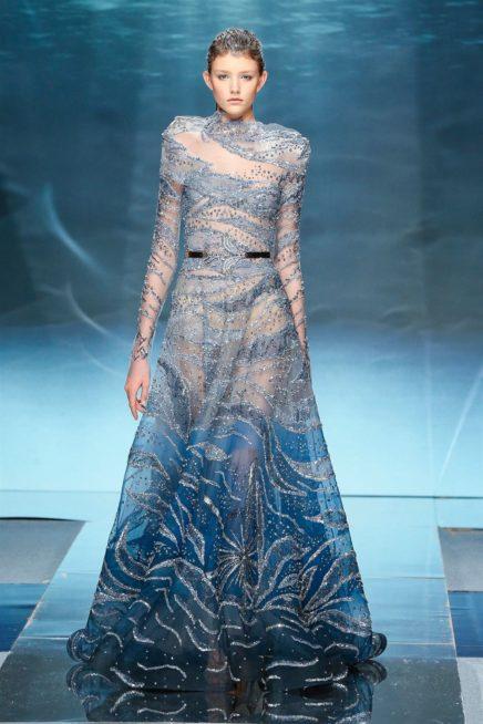 """<p dir=""""RTL""""><span lang=""""AR-LB"""">نشعر للحظة عند رؤيتنا لهذا الفستان انّنا اصبحنا فعلاً تحت الماء نبحث عن مدينة اتلانتس الضائعة بين الامواج. انه قطعة فنيّة حقيقة تعكس فنّ الخياطة الراقية باجمل طريقة.</span></p>"""