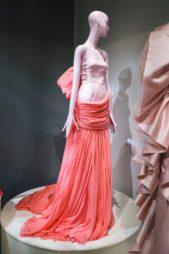 فستان طويل بلونين مختلفين متناسقين بطريقة مبتكرة حيث صمم القسم العلوي باللون الزهري مع القصة الضيقة ذات الاكتاف المكشوفة، والقسم السفلي باللون الزهري الداكن المنسدل بقصة واسعة ناعمة.