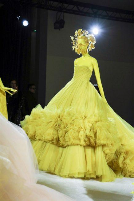 فستان طويل مميز بقصته الواسعة جداً عند الاسفل، ذات اللون الاخضر الباهت تميّزه الكسرات الضيقة الجانبية، في حين زيّن القسم السفلي منه بالكشاكش الصغيرة العديدة.