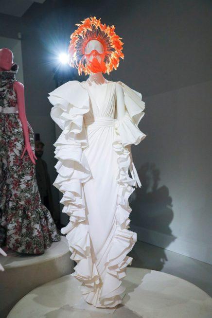 فستان طويل أبيض اللون ذات القصة الضيقة المتجانسة مع شكل الجسم، تجمّله الكشاكش الكبيرة الموزّعة عند الجانبين والكتفين لتضفي الجرأة والفرادة إلى الاطلالة، في حين برزت الفتحة V الواسعة عند الصدر.