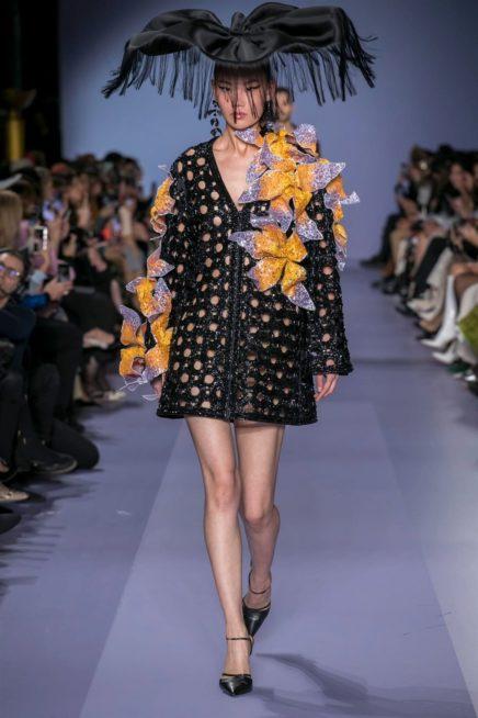 """<p dir=""""RTL""""><span lang=""""AR-LB"""">فستان قصير أسود مصنوع من القماش الجامد، يتميّز بالدوائر المفرّغة فيه، وتنسدل الازهار المصنوعة يدوياً على الاكمام. فيما تأتي القبعة ضخمة جداً وتنسدل منها الشراشيب لتعكس الاجواء الاحتفالية.</span></p>"""
