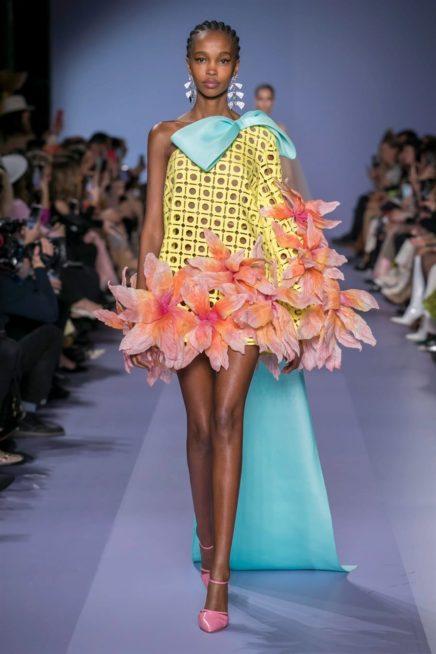 """<p dir=""""RTL""""><span lang=""""AR-LB"""">فستان اصفر قصير ذات دوائر مفرّغة، يتزيّن كتف واحد فيه بفيونكة زرقاء كبيرة، فيما أضيفت الازهار ذات الحجم الكبير الى اطرافه السفلية لتغنيه وتزيده جمالاً.</span></p>"""