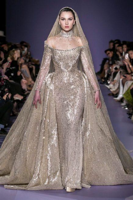 """<p dir=""""RTL""""><span lang=""""AR-LB"""">عروس جورج حبيقة لربيع وصيف 2020 متألقة باللون الذهبي الرائع مع التطريزات البراقة التي تزيّن الفستان كلّه. وهو يأتي بقصّة ضيقة لكن مع شلحة تنسدل من الخصر، فيما الكورسيه ذات جزء علوي شفاف يزيد من انوثة التصميم.</span></p>"""