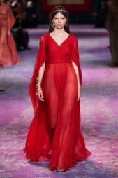 فستان أحمر طويل مصمم من القماش الشفاف ويتميز بقصته المنسدلة بتناغم مع الجسم تجمّله الأكمام الطويلة الواسعة مع الفتحة الناعمة عند الصدر.
