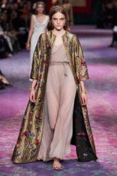فستان طويل باللون البنفسجي الفاتح ذات القصة الرومانية القديمة منسّق بطريقة متقنة مع المعطف الذهبي الطويل المزين بتطريزات الازهار الملونة.
