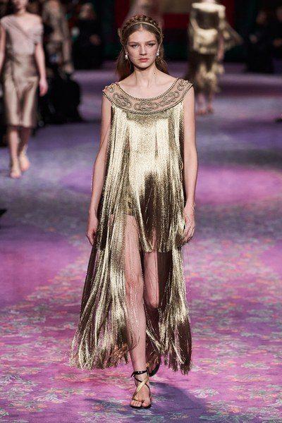فستان طويل بقصة رومانية واسعة مميز بالشراشيب الطويلة المنسدلة من الاعلى الى الاسفل، مع الزخرفات والتطريزات الذبية عند الكتفين والصدر.
