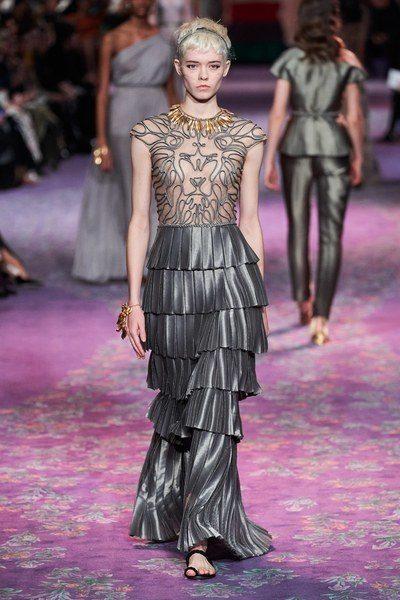 فستان طويل ضيق بقصة الحورية ذات اللون الفضيّ، تجمّله الطبقات المختلفة من الكسرات العريضة مع الزخرفات الناعمة عند الصدر لانوثة ملفتة.