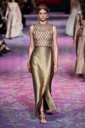 فستان طويل ضيّق ذهبي اللون يجمّله الشق الجانبيّ العالي مع التصميم الشبك عند الصدر وأشكال الحبال المتجانسة عند العنق.