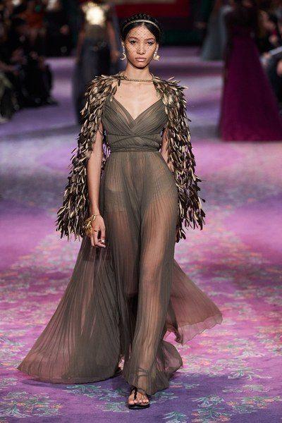 فستان طويل مصمم من القماش الشفاف باللون الزيتي ذات القصة المتناغمة مع الجسم يجمّله الكاب الذهبي القضير المصمم من اوراق الغار.