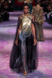 فستان طويل مميز بتداخل اللونين الازرق الداكن والذهبي اللماع تجمّله الشراشيب الطويلة المنسدلة من الخصر الى الاسفل مع الكاب الشفاف الطويل.