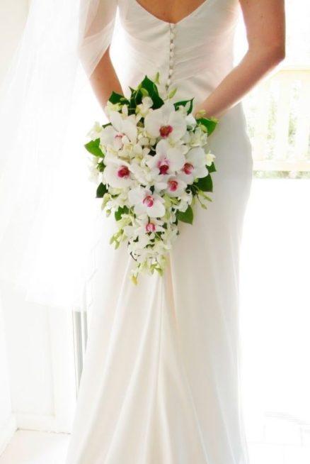 لإطلالة بقمة الأناقة في زفافك، إختاري مسكة الأزهار الجذابة والمنسدلة بلونها الأبيض وزيّني جوانبها ببعض الأوراق الخضراء تماماً كما تلاحظين في الصورة.
