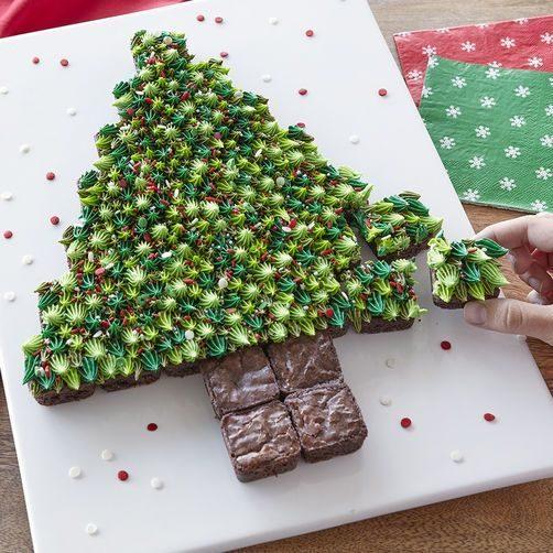 وزعي البراونيز بالشوكولاته على صينية بيضاء وبشكل شجرة الميلاد وزينيها بالكريما الخضراء وبعض الحبيبات الملونة.