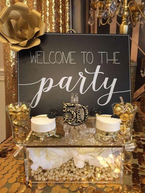 اختاري لافتة ترحيب بالحضور وضعيها على طاولة مزينة باللون الذهبي تحمل عدد سنوات الزواج لتضفي فرادة اكبر على الديكور.