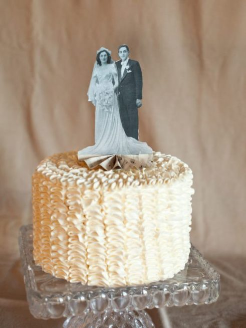 فكرة مبتكرة لتزيين قالب الحلوى لعيد الزواج مع استعمال صورة قديمة لكما خلال حفل الزفاف ووضعها اعلى القالب باللونين الابيض والاسود.