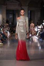 <p><strong>Rami Kadi - رامي القاضي </strong></p> <p>فستان طويل بقصة الحورية مناسب للسهرات الشتوية الصاخبة يتميز بلونه الفضي اللماع المتناسق مع اللون الاحمرالبراق.</p>