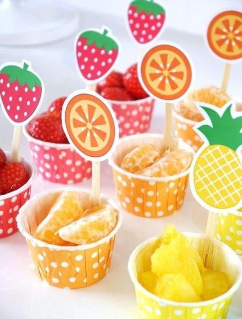قدّمي الفواكه لضيوفك بطريقة مبتكرة من خلال وضعها في اكواب من الكرتون وتزيينها برسمة الفاكهة عينها اعلى الكوب.