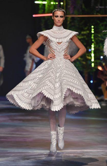 فستان ابيض اللون بقصة الكلوش الواسعة مع الزينة البيضاء التي تغطيه بالكامل تميّزه الياقة العالية والاكمام على شكل كاب عند الاكتاف.