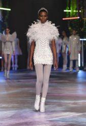 فستان قصير باللون الابيض ذات القصة الضيقة مع الريش الذي يغطي العنق والاكتاف والصدر نسق بطريقة متقنة مع الجوارب البيضاء.