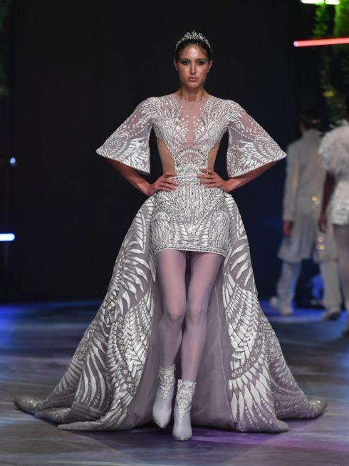 فستان قصير باللون الفضي مزين بالنقشات البيضاء يتميز بأكمامه الواسعة والفتحتين عند الخصر، مع الشلحة الطويلة والعريضة من الخلف.